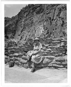 [Helen Moore sitting at the base of a cliff in Frijoles Canyon, New Mexico]