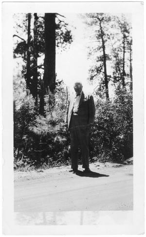 Primary view of object titled '[Col. Hugh B. Moore walking along a dirt road]'.