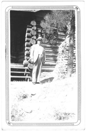 Primary view of object titled '[Col. Hugh B. Moore in front of the Moore cabin at the Rainy Day Ranch in New Mexico]'.