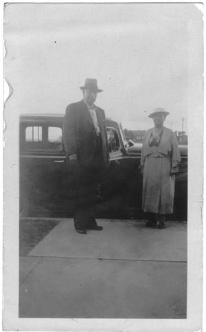 [Col. Hugh B. and Helen Moore standing in front of a car]