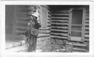 Primary view of object titled '[Helen Moore holding a stringer of fish in front of a cabin]'.
