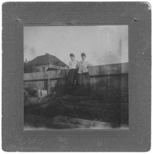 Primary view of object titled 'Two Women Standing Against a Fence'.