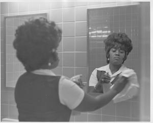 Female Custodian Cleaning Mirrors