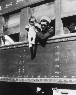 Primary view of object titled '[Emzie Fisher  on Train Holding His Son During World War II]'.