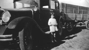 [A Child Standing near a Car with a Trailor]