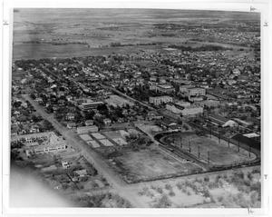 Sky high view of a football field, with blocks of houses in the background.