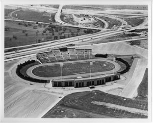 Top view of a football field mostly constructed with the highway roads seen  behind it.