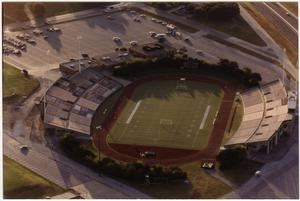 Colored photo of an empty football field with a mostly empty parking lot. A few cars are parked outside of it.