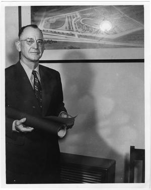 Man in a suit and glasses holds a roll of paper and stares at camera. An aerial photo of a field is seen partially behind him