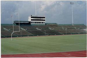 Picture in color of the inside of a football field, empty field and bleachers with the word Eagles on the side of a tower.