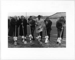 Six men all in suits hold a shovel in each of their hands, with the end of the shovel stuck in the ground and a bow tied around it.
