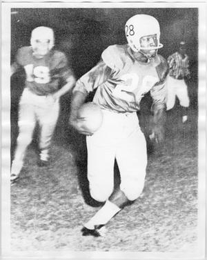 Old black and white photo of a black man holding a football. Another player is seen blurry close in the background, another man in a striped ref's uniform is seen in the right.