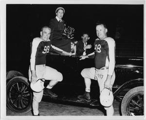 2 mujeres con faldas y tacones posan de rodillas y sostienen micrófonos con las letras NT en sus manos derechas. Ambas tienen el pelo corto y oscuro.