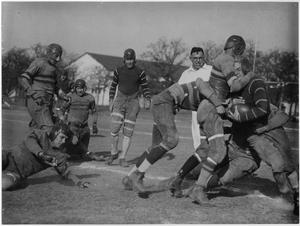 Black and white photograph of 7 members of a football team in motion. Three  are tackling the other, as a man in all white stands behind them, staring, in the near back.
