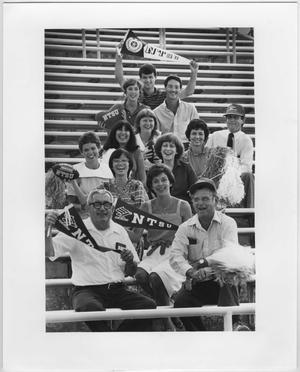 13 personas sentadas en 8 filas con algunos sosteniendo pancartas de NTSU, Todos sonríen y son mayores.
