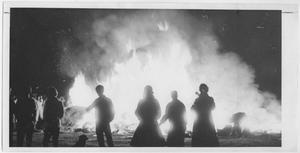 Outline of 6 people in front of a tall bonfire.