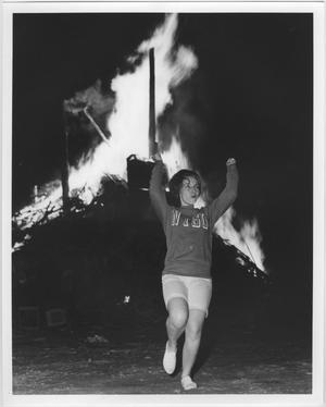 Girl with short hair, in shorts and NTSU sweater, has both arms raised in air as she stands in front of the bonfire.