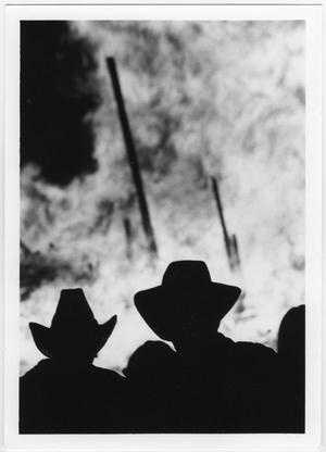 Outline of two men in hats from shoulders up, standing in front of a bonfire with large slabs of wood sticking out.