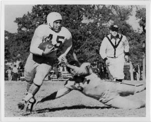 Old photograph of one man attempting to tackle another. A man in a coaches uniform is seen running towards them. Trees cover the background.