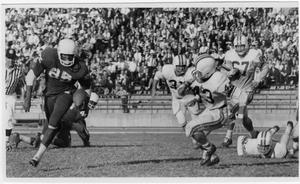 Black and white photo. Players in white uniform are seen on the right, chasing a player in black. The sideline crowd is full and seen in the background.