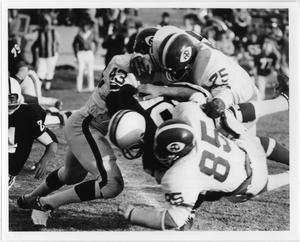 Black and white photo of men in white uniform tackling each other.