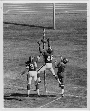 3 men jump, the one in the middle throws a football into the air right by the field goal. The one in the middle is seen higher in the air then the two on his side.