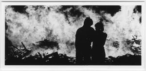 Outline of a man and a women with their arms around each other, standing in front of a bonfire.