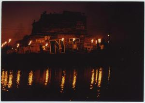 Stacks of wood are seen layered on top of each other, with the reflection of it in the water. The letters N and T are in front of it, with people standing in front of it with torches.