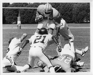 4 men tackle another. Man in the middle is holding football in his right hand and jumps high above the others.