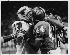 One football player holds another closely by the shirt. Ref in striped shirt tries to pull them apart.