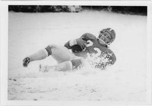 Football player laying in snow covered ground with football cradled in his right arm.