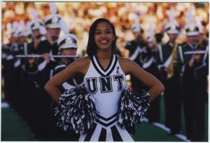 Una animadora afroamericana con un uniforme verde y blanco posa con pompones en sus manos a su lado. Un grupo de miembros de la banda puede verse  en el fondo.