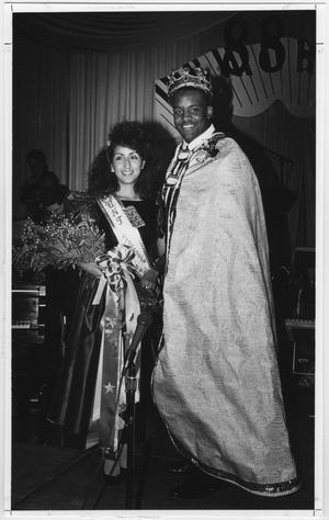 Man and woman seen standing next to each other. Woman on the left has a sash and holds a bouquet of flowers. Man on the left has a crown on his head and wears a robe.