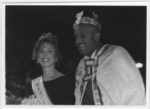 Caucasian woman is smiling on the left, with a sash and crown on her head. African-American man to the right of her smiles, wearing a crown on his head and a robe.