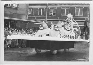 5 mujeres con pelo corto y vestidos se sientan encima de una carroza con las palabras la Reina de la Fiesta de Exalumnos en el lado derecho. Sonríen mientras la carroza pasa por delante de una multitud de personas a la izquierda frente a una tienda.