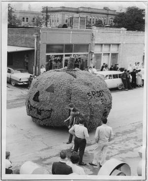 A float that looks like a pumpkin is in the middle of the road. 4 men stand around it in front of a store by the name of King's Flowers.