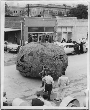 Una carroza con forma de calabaza se encuentra en medio de la carretera. 4 hombres están de pie alrededor de ella frente a una tienda llamada Las Flores del Rey.