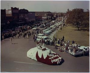 A white and red float with the words Texas Norm on the front is at the  front of the street. Cars and people line up the side of the road, with  men in uniform marching down the middle.