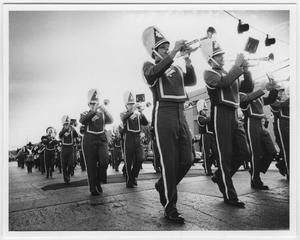 Hombres en uniforme de banda con grandes sombreros tocan sus trompetas mientras marchan. Fotos tomadas desde un ángulo inferior.