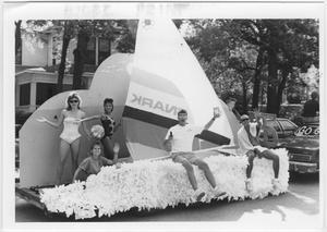 Grupo de 4 mujeres y 2 hombres sentados y de pie en una carroza hecha como un velero con plumas blancas en la parte delantera.