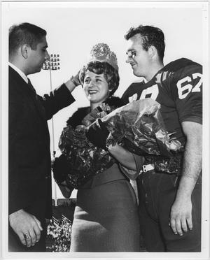 Women with a bouquet of flowers in her arms wears a crown. She stands next to a smiling man on her right in a football uniform, and a man to her left in a suit with his hand on the crown.