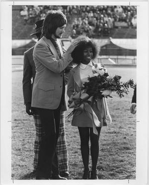 Black and white photo of an African American woman wearing a dress and holding flowers in her arms. Next to her on the left of the photo is a man in a suit, with a mullet. He has hos hands on her hair. Behind him stands another man, who cannot seen by the face. In the background are people in the stands in the far back.