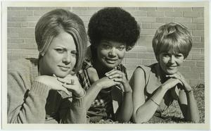 Three women pose with their hands under their chin. The woman in the middle is an African American women, and the two on the right and left of her are caucasian.