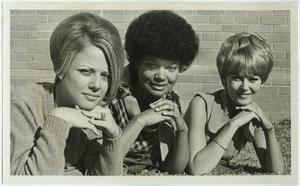Tres mujeres posan con las manos bajo la barbilla. La mujer del centro es una mujer afroamericana, y las dos que están a su derecha e izquierda son caucásicas.