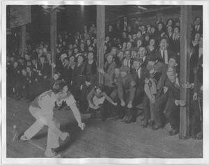 Un hombre vestido de blanco se encuentra frente a una multitud de personas que gritan en las gradas. El hombre se inclina hacia su derecha mientras los mira.