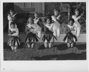 8 animadoras saltan en el aire con las piernas hacia atrás. Los 4 de delante frente son mujeres y los 4 de atrás son hombres. Tienen los brazos cruzados.