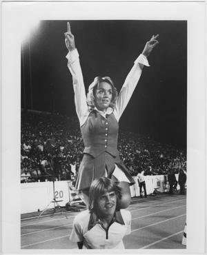 Un hombre con flequillo y pelo de longitud media y con una camisa blanca se inclina un poco hacia delante. Una mujer con camisa y falda está a su espalda con los brazos levantados hacia arriba.
