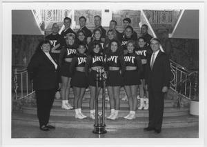 Un grupo de animadoras posa en las escaleras en filas de tres. Un hombre y una mujer trajeados se sitúan en lados opuestos a ellas. Un trofeo gigante está entre ellos.