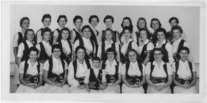 Un grupo de 27 mujeres está en 3 filas sentadas o de pie cerca unas de otras. Todas llevan una falda y una camisa blanca con un chaleco negro.