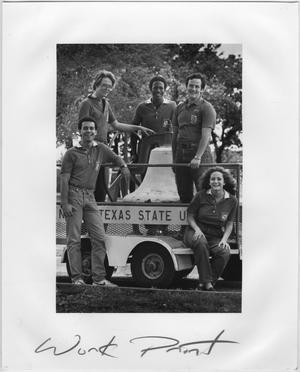 Una fotografía está en una página blanca con las palabras Trabaja Imprime. En la foto 3 hombres están de pie dentro del vehículo sosteniendo una gran campana y un hombre posa fuera con el brazo sobre el vehículo. Una mujer está sentada en el vehículo.